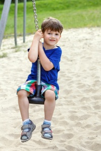 Happy little boy sit on swing rope